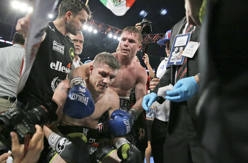 Liam Smith, left, is hugged by Canelo Alvarez after their WBO Junior Middleweight championship boxing match at the stadium in Arlington, Texas, Saturday, Sept. 17, 2016. Alvarez won by a knock out in the ninth round. (AP Photo/LM Otero)